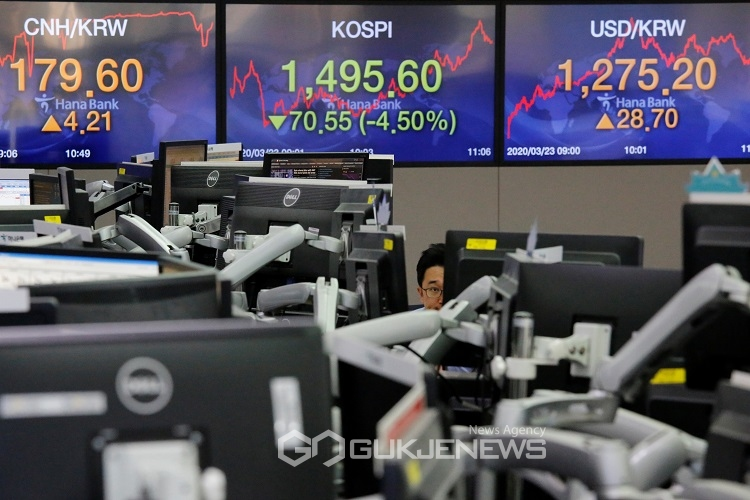 A currency dealer works in front of electronic boards showing the Korea Composite Stock Price Index (KOSPI) and the exchange rate between the U.S. dollar and South Korean won, in Seoul