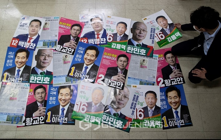 An official from the National Election Commission checks posters for candidates of upcoming parliamentary election in Seoul
