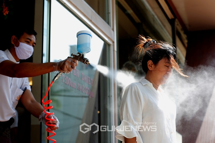 A coffee shop staff sanitizes a customer as a precaution due to the coronavirus disease (COVID-19) outbreak in Yangon