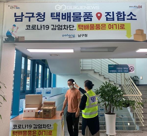 포항시 남구 자치행정과 직원이 청사 입구에서 물품 배달 온 택배사 직원에게 발열체크를 하고 있다.(사진 포항남구청)