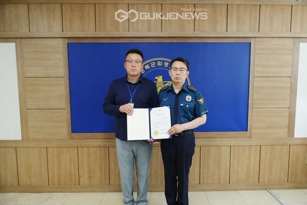 박효식 군위경찰서장(우측)이 형사팀 이제헌 경위에게 유공자 표창을 수여하고 사진을 찍고 있다. (사진 군위경찰서)