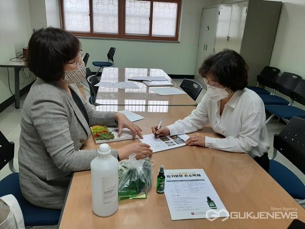 사진=수원시자원봉사센터 소속 교육강사단 봉사자가 영덕중학교 교사에게 슬기로운 손소독제 만들기를 설명하고 있다.