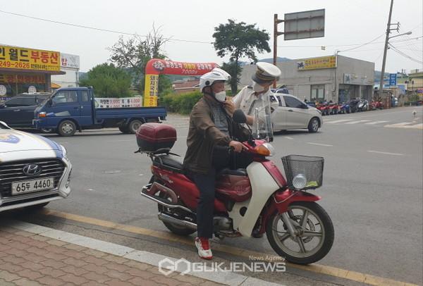 경산경찰서 경찰관이 3일 자인시장을 방문한 고령 오토바이 운전자에게 안전모를 전하며 안전운전을 당부하고 있다(사진=경산경찰서)