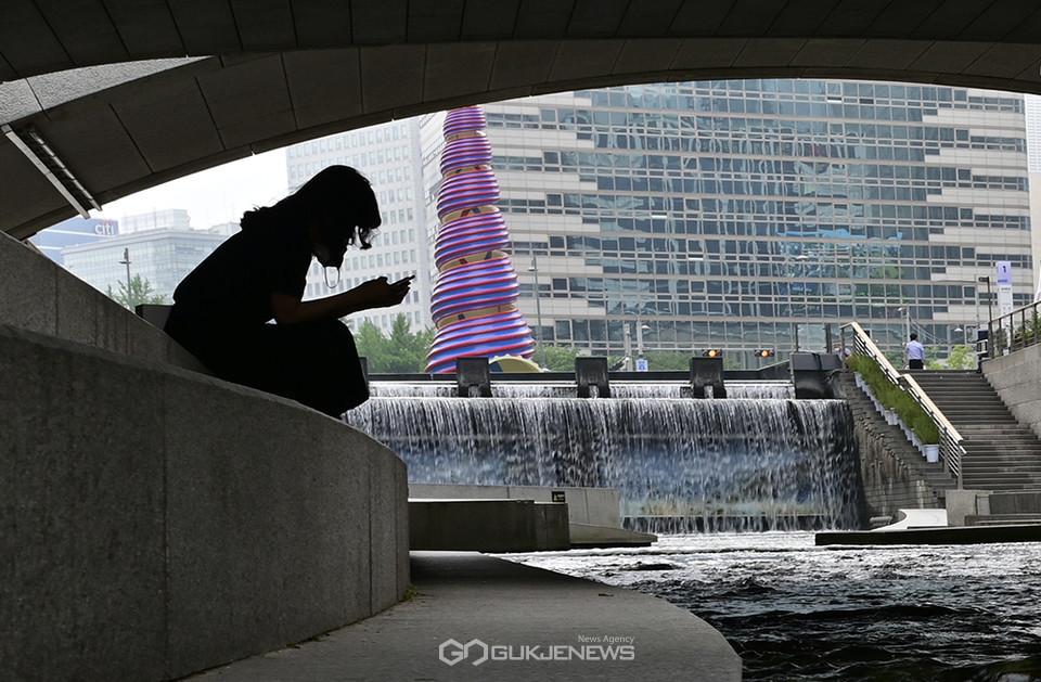 (사진=안희영 기자) 청계천에서 휴식을 취하고 있는 시민.