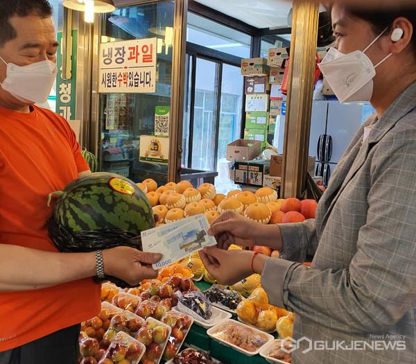 사진 = 캄보디아 출신 결혼이민자가 성남 중앙시장에서 성남사랑상품권으로 수박을 사고 있다