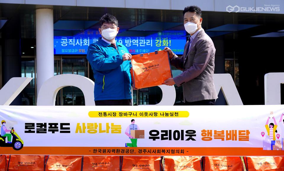 차성수 한국원자력환경공단 이사장이 김종우 경주시사회복지협의회장에게 행복장바구니를 전달하고 있다