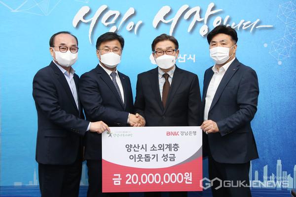 (사진제공=BNK경남은행) BNK경남은행 최홍영 은행장(왼쪽 두번째)이 양산시 김일권 시장(오른쪽 두번째)에게 '소외계층 이웃돕기 성금 기탁 증서'를 전달하고 있다.