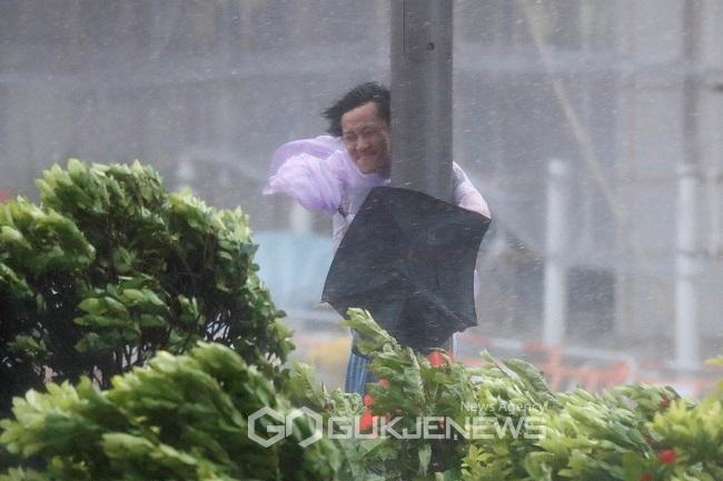 한 남성이 강풍에 날아갈까 전봇대를 붙들고 있다. (로이터/국제뉴스)