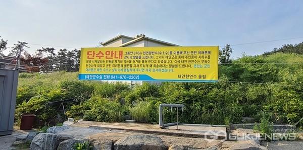 태안천연수 측이 태안군의 '지하수 양성화' 불허가 처분에 반발하며 내건 '단수 안내' 현수막. (사진 = 최병민 기자)