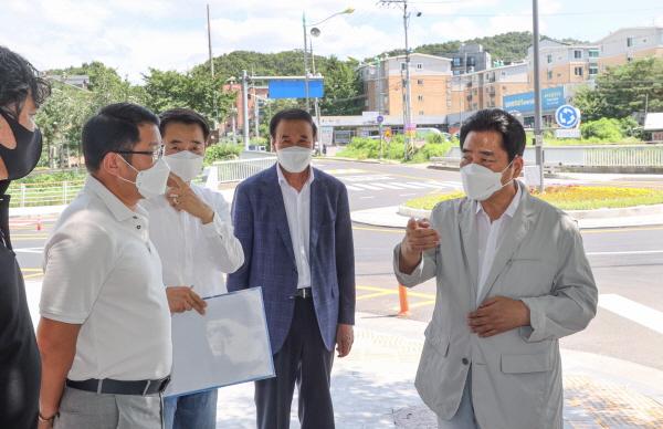 (사진=용인시)백군기 용인시장이 18일 모현읍 왕산리 모현교사거리에 설치된 도심형 회전교차로를 살피고 관계자들과 이여기를 나누고 있다.