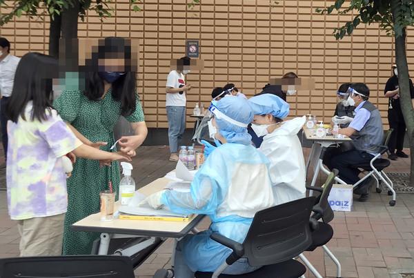 마스크를 쓴 많은 시민들이 코로나19 검사를 실시하기위해 길게 줄지어 서 있다. (국제뉴스DB)
