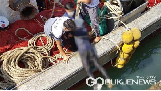 충남 태안해양경찰서 신진파출소 순찰팀 대원이 어선 선원들과 함께 호줄에 매달린 50대 남성을 배 위로 끌어올리고 있다.(태안해경 제공)