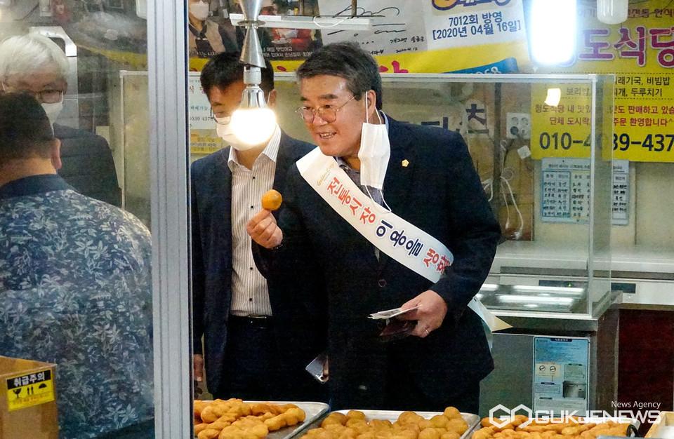 (사진=김진태 기자) 전통시장에서 시설 아동에게 나눠줄 도넛을 구매후 맛을 보는 서호대 의장