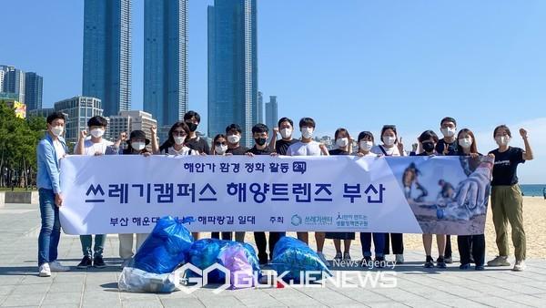 해안가 쓰레기 수거 활동 후 종이현수막과 함께 기념촬영을 하고 있다.